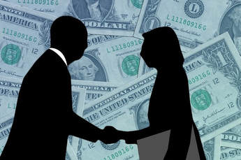 Two career professionals are silhouetted shaking hands, a man and a woman.